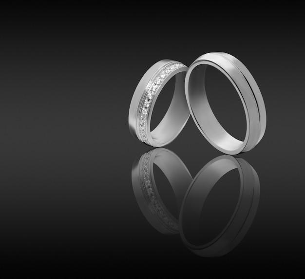 暗い表面のカップルの結婚式の婚約指輪