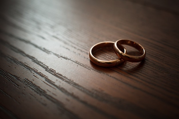 Couple of wedding rings on wooden table
