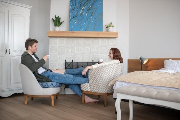 カップル、幸福。暖炉のそばで自宅でコーヒーを飲みながら、裸足で向かい合って座っているカジュアルな服を着た若い大人の笑顔の男と女
