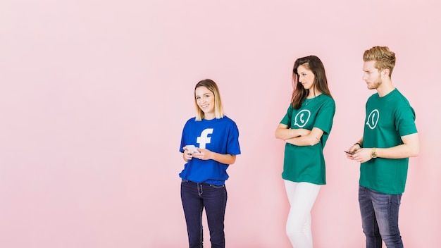 Couple in whatsapp t-shirt looking at happy woman wearing facebook top