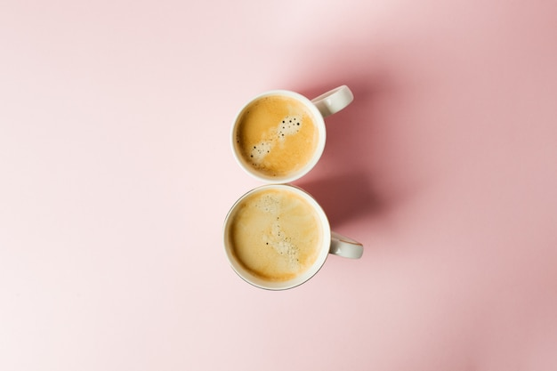 Couple white cups with coffee on pink pastel background, 8 march celebration minimal concept