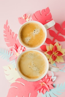 Couple white cups with coffee on pink pastel background with origami modern paper craft flowers
