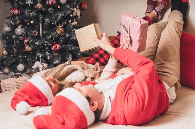 Пара, жена и муж обмениваются рождественскими подарками