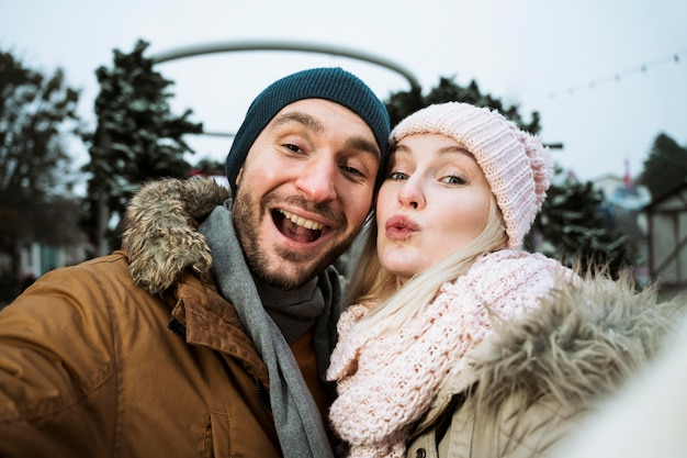 Couple in winter blowing a kiss