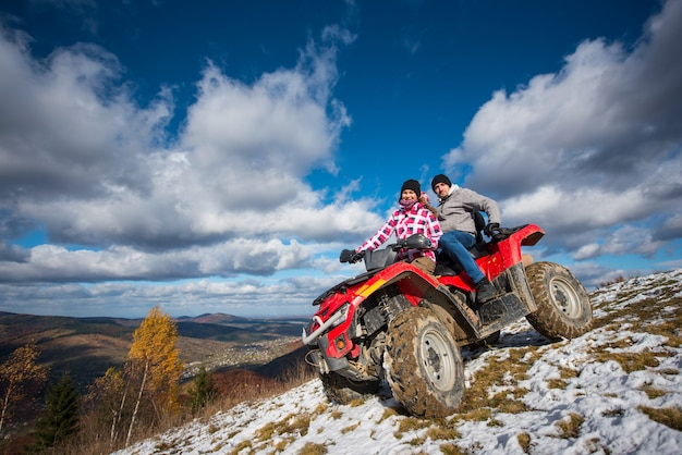 Couple in winter clothes riding on a red atv on a mountain slope
