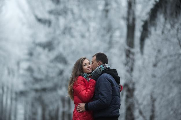 Coppia nella foresta invernale vicino al lago