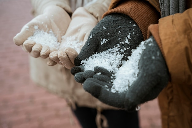 Couple in winter holding snow in their hands