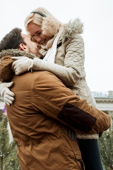 Couple in winter hugging low view