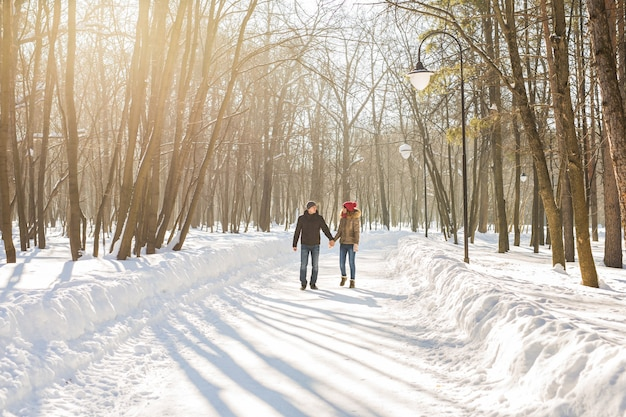 Couple on winter path in forest on a sunny day.
