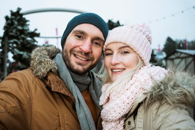 Coppia in inverno sorridendo alla telecamera