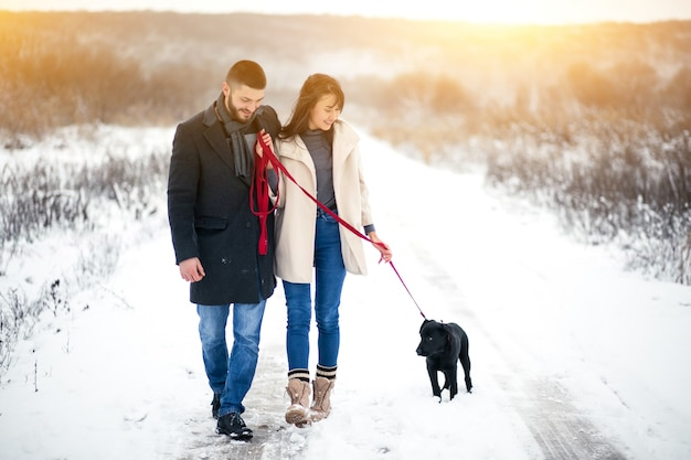 Couple in winter in the street with dog