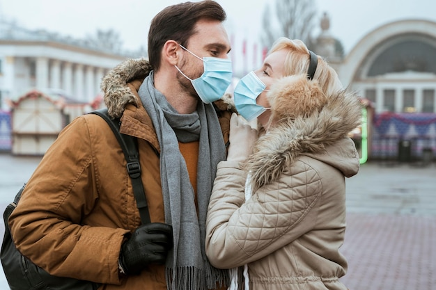 Couple in winter wearing medical masks and hugging