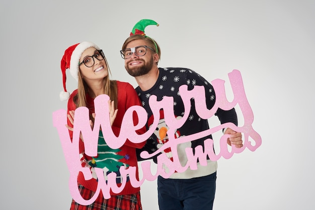 Couple wishing merry christmas to all