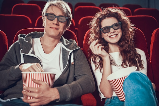 Couple with 3d glasses eats popcorn and sitting in cinema.