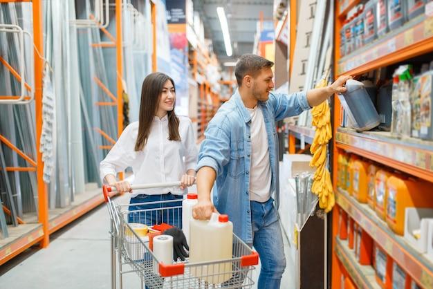 Пара с тележкой выбирает стройматериалы в строительном магазине. покупатели смотрят товары в магазине своими руками