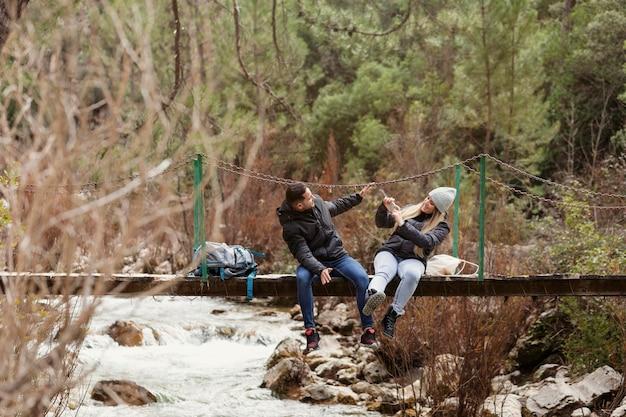 Couple with backpack sitting on bridge