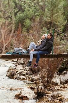Coppia con zaino seduto sul ponte