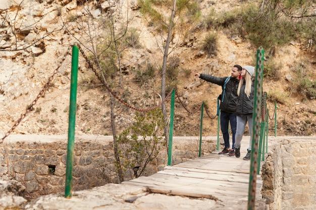 Coppie con lo zaino che camminano sul ponte