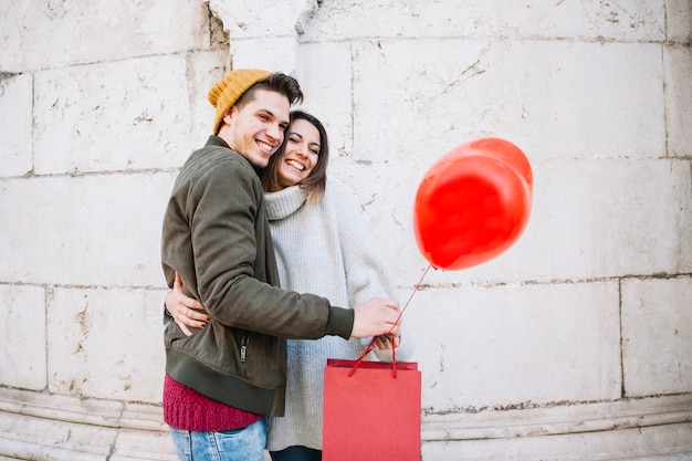 Couple with balloon and paper bag hugging