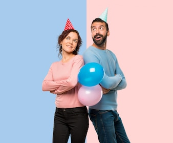 Couple with balloons and birthday hats looking up while smiling on pink and blue background