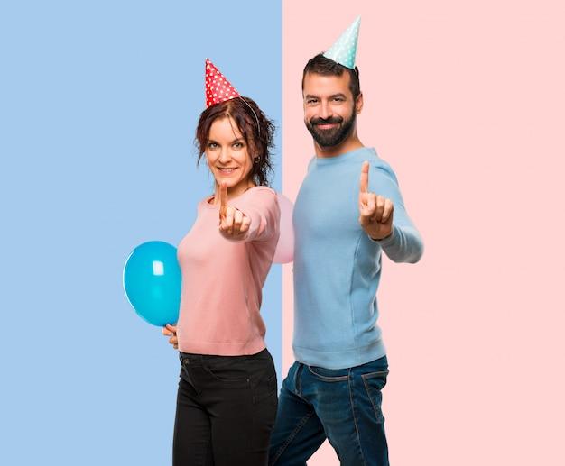 풍선 및 생일 모자 표시 및 최고의 표시에 손가락을 해제 커플