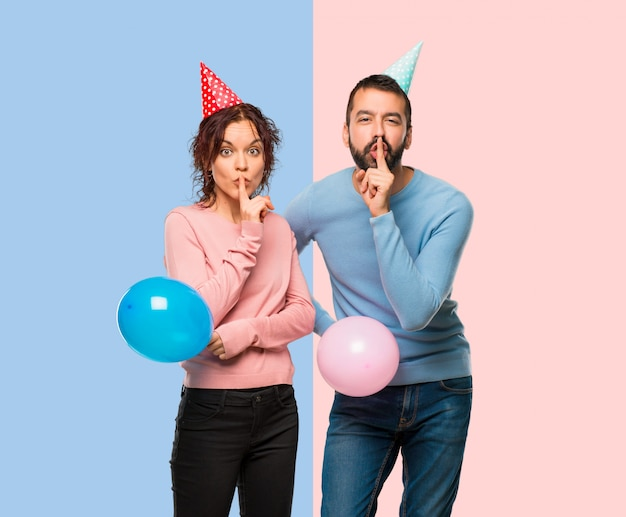Couple with balloons and birthday hats showing a sign of silence gesture putting finger in