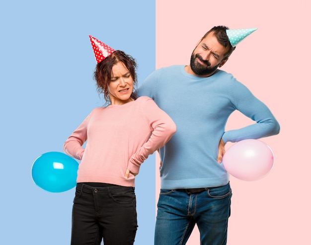 Couple with balloons and birthday hats suffering from backache for having made an effort