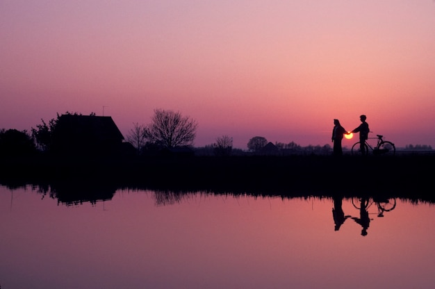 Couple with bicycle holding hands silhouetted against sunset sky standing on shore of remote lake