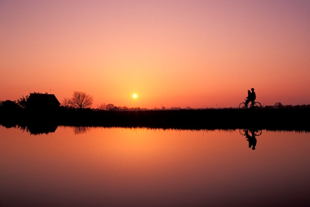 Couple with bicycle silhouetted against sunset sky standing on shore of remote lake