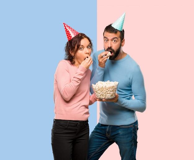 誕生日の帽子とカップルとピンクと青の背景にポップコーンを食べる
