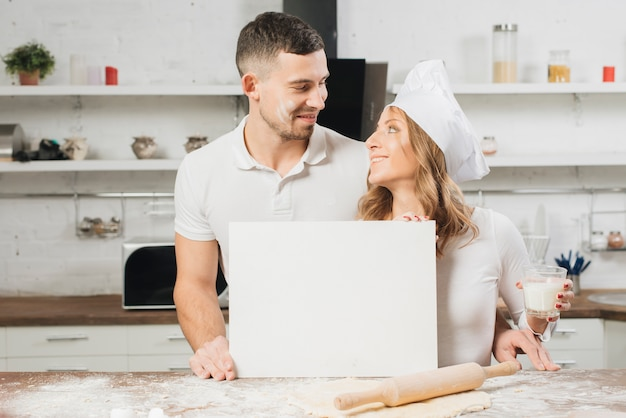 Couple with blank paper in kitchen