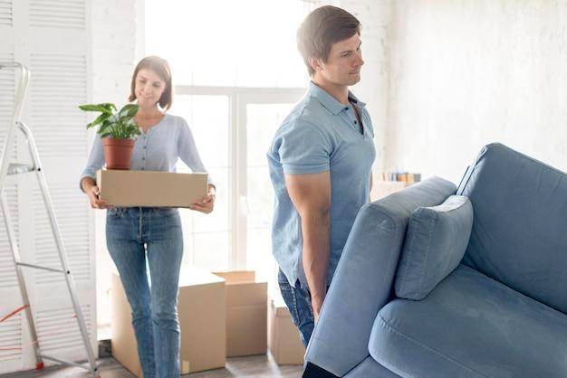 Coppia con scatole e divano in procinto di uscire