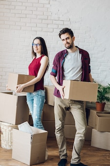 Couple with boxes in empty room