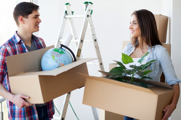 A couple with boxes moves to a new house. property for sale.