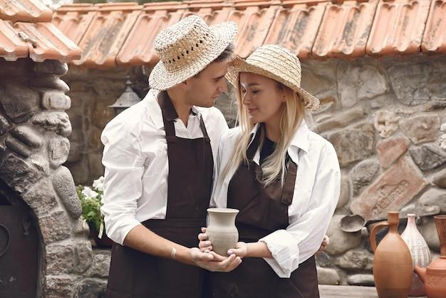 Пара с коричневыми фартуками и держа вазу