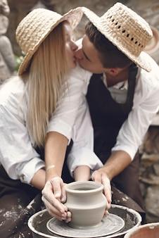Пара с коричневыми фартуками делает вазу