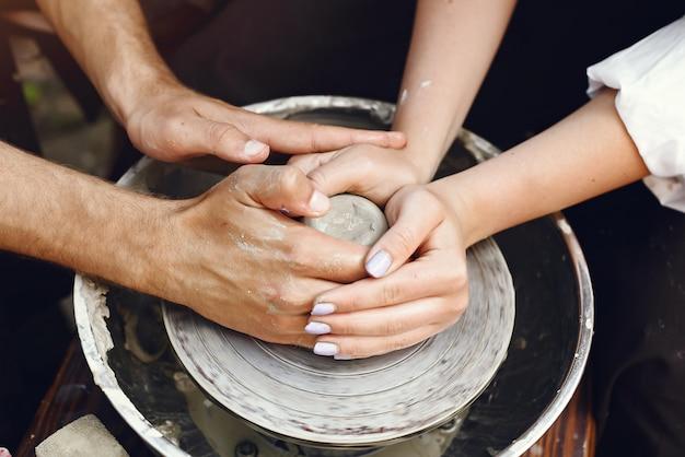 Coppia con grembiuli marroni facendo un vaso