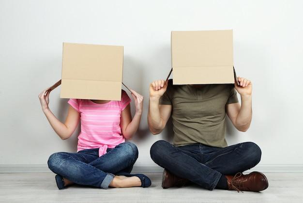 벽 근처 바닥에 앉아 그들의 머리에 골 판지 상자와 커플