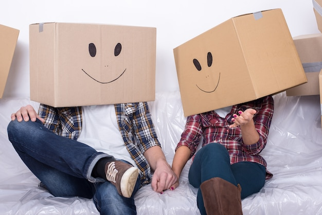 Couple with cardboard boxes on their heads with smiley face