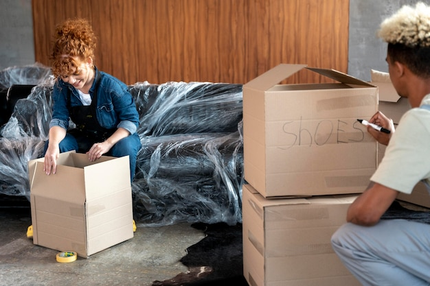 Couple with cardboard boxes in their new home