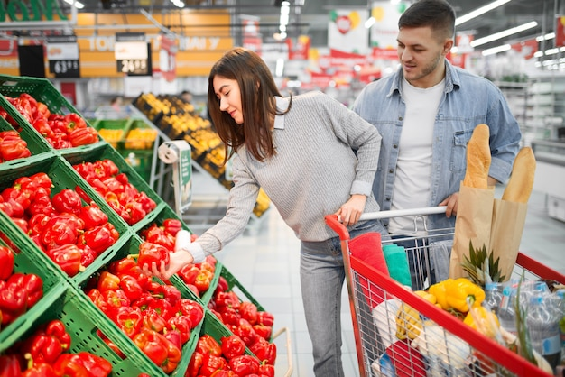 Couple with cart choosing fresh sweet red peppers in a supermarket