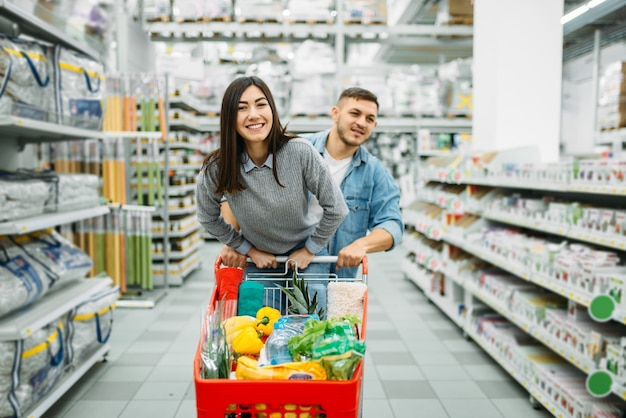 Couple with cart full of goods in a supermarket