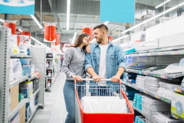 Пара с тележкой в супермаркете, семейные покупки