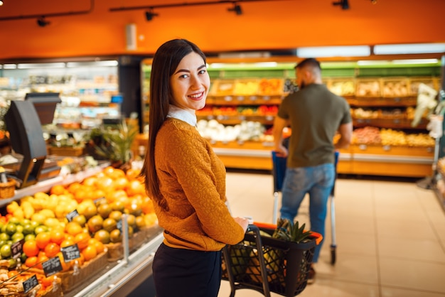 Пара с тележкой в продуктовом супермаркете вместе