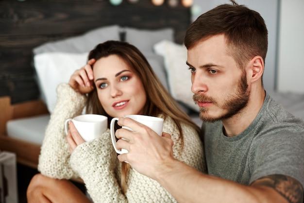 Coppia con caffè seduta sul pavimento in camera da letto