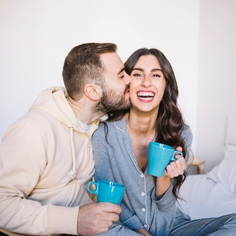 Couple with cups kissing