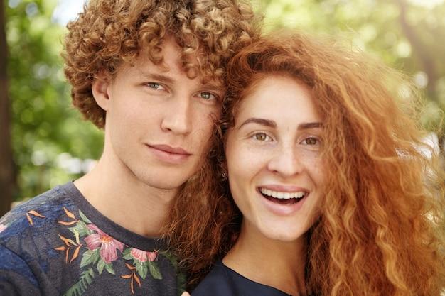 Coppia con capelli rossi ricci che si distendono all'aperto