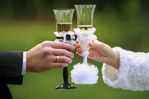 Couple with decorated wine glasses on their wedding day close up. two decorated black and white glasses with champagne on green outdoors. hands of bride and groom holding  glasses close up