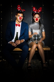 Couple with deer antlers headbands and funny noses with bottle and disco ball