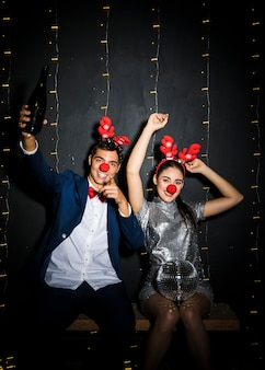 Couple with deer antlers headbands and funny noses with disco ball and bottle